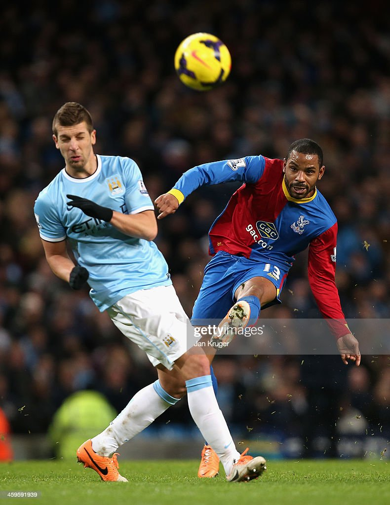 Jason Puncheon of Crystal Palace shoots past Matija Nastasic of Manchester City during the Barclays Premier League match between Manchester City and Crystal Palace at the Etihad Stadium on December 28, 2013 in Manchester, England.