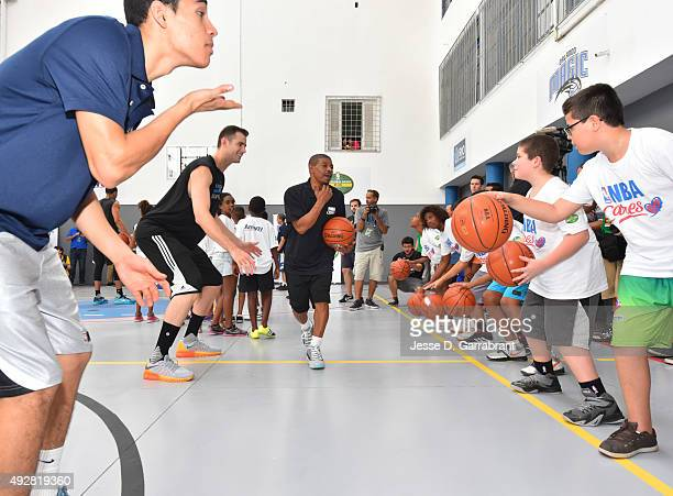 Jason Smith and of the Orlando Magic and former NBA player Muggsy Bogues run a drill during a NBA Cares Court Refurbishment sponsored by AMWAY during...