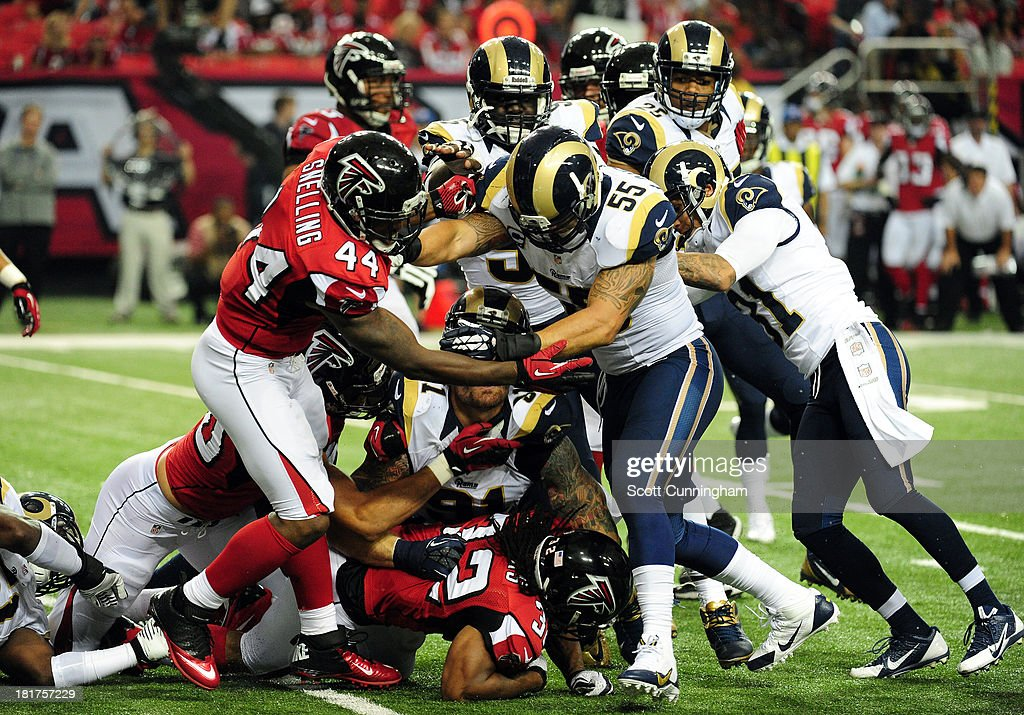 Jason Snelling of the Atlanta Falcons blocks against James Laurinaitis of the St Louis Rams at the Georgia Dome on September 15 2013 in Atlanta...