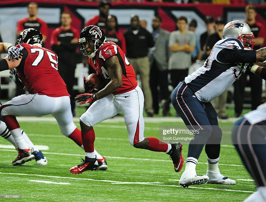 Jason Snelling of the Atlanta Falcons carries the ball against the New England Patriots at the Georgia Dome on September 29 2013 in Atlanta Georgia