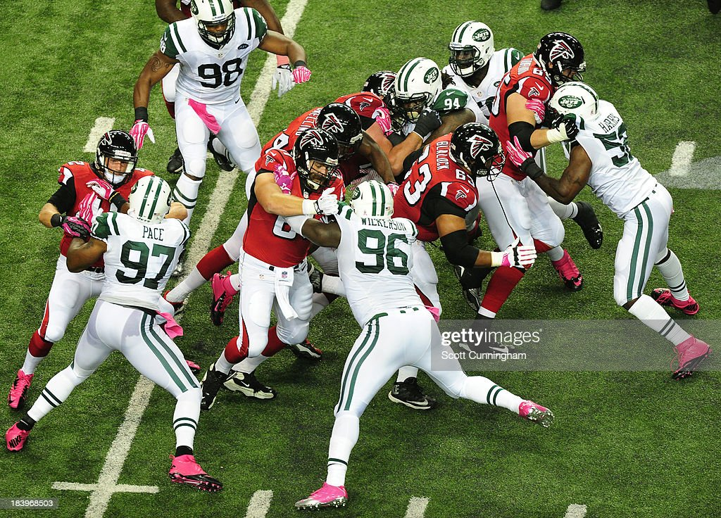 Jason Snelling of the Atlanta Falcons carries the ball behind blocking by Justin Blalock Joe Hawley and Jeremy Trueblood against the New York Jets at...
