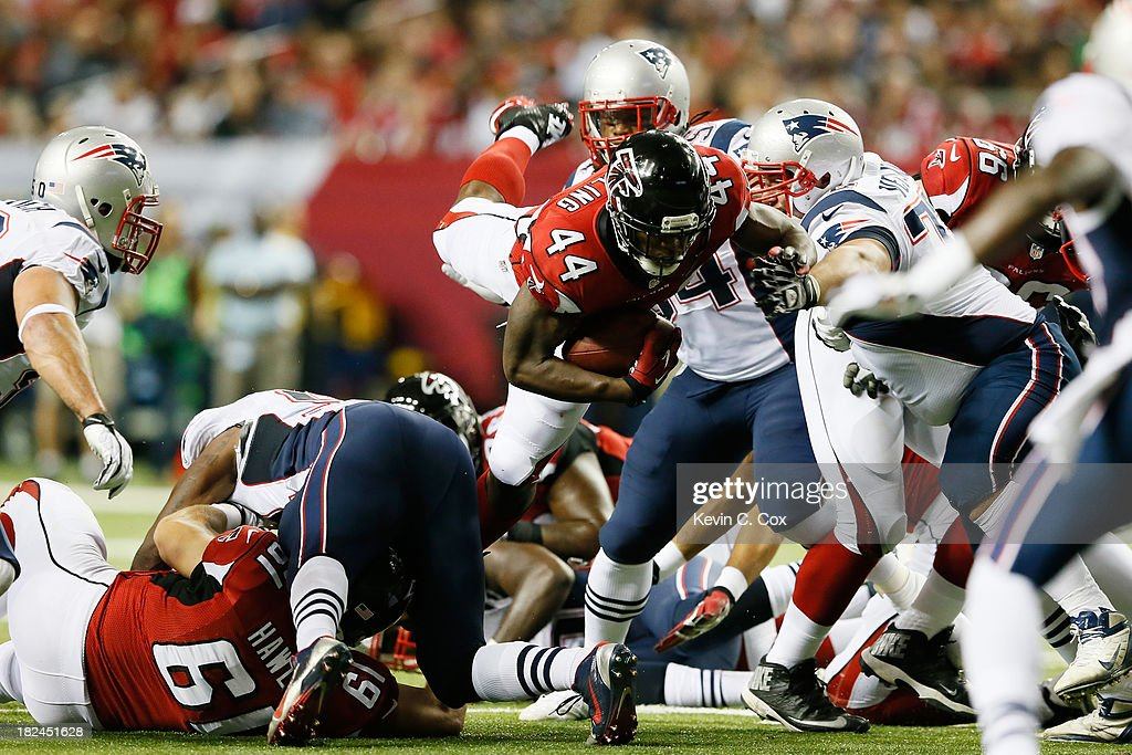 Jason Snelling of the Atlanta Falcons dives for a first down against the New England Patriots during the game at Georgia Dome on September 29 2013 in...