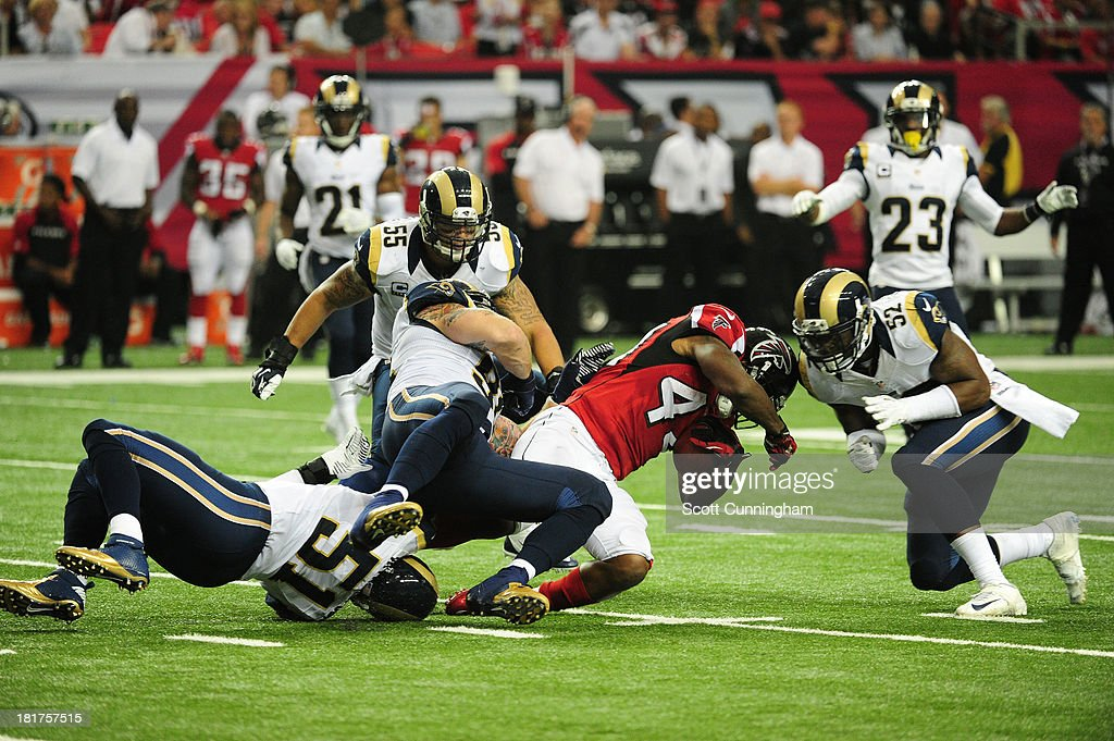 Jason Snelling of the Atlanta Falcons is tackled by Chris Long and Alec Ogletree of the St Louis Rams at the Georgia Dome on September 15 2013 in...