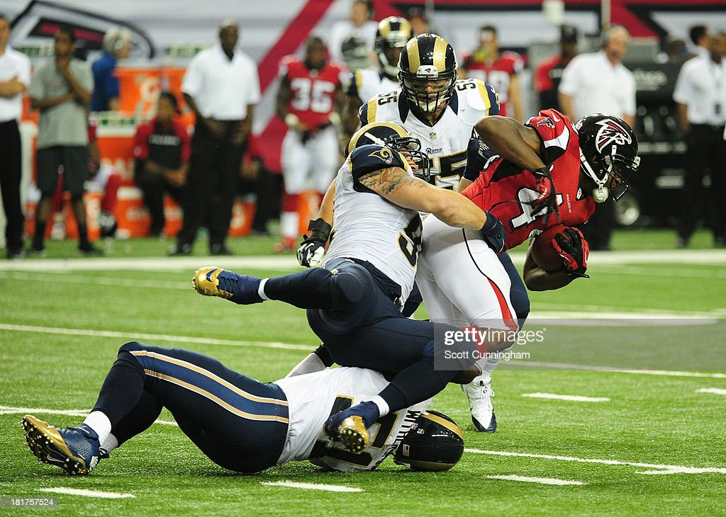 Jason Snelling of the Atlanta Falcons is tackled by Chris Long of the St Louis Rams at the Georgia Dome on September 15 2013 in Atlanta Georgia