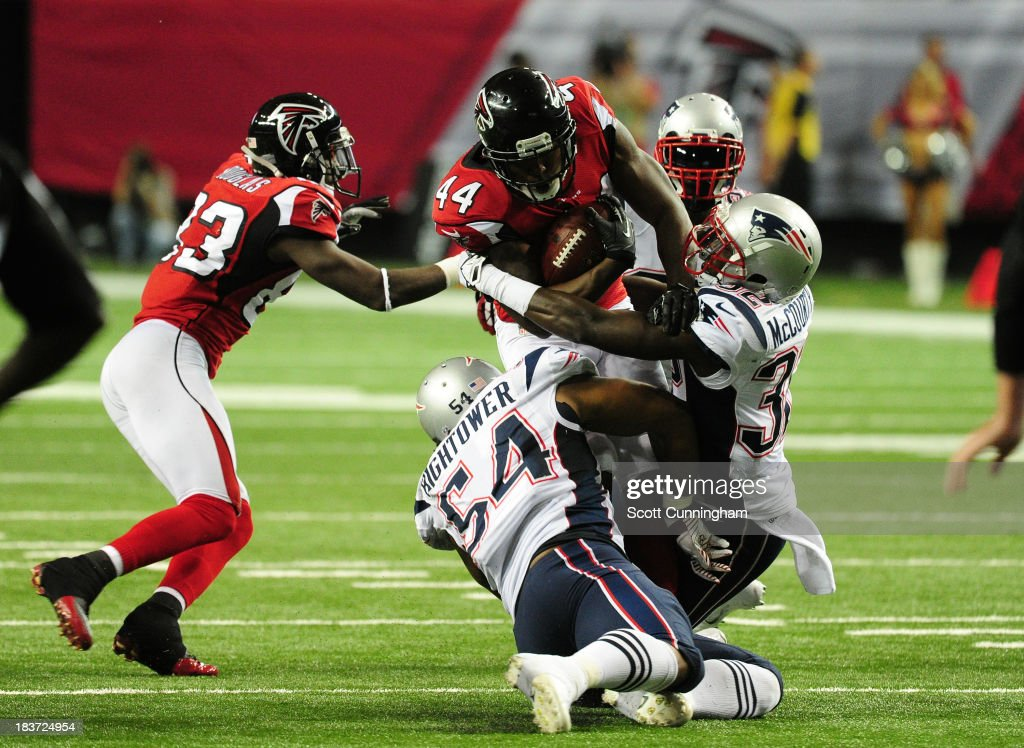 Jason Snelling of the Atlanta Falcons is tackled by Devin McCourty and Dont'a Hightower of the New England Patriots at the Georgia Dome on September...