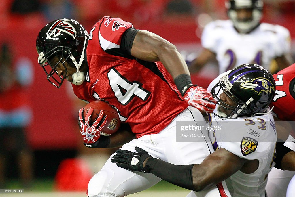 Jason Snelling #44 of the Atlanta Falcons rushes against Jameel McClain #53 of the Baltimore Ravens at Georgia Dome on September 1, 2011 in Atlanta, Georgia.