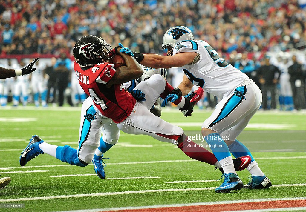 Jason Snelling of the Atlanta Falcons scores a first quarter touchdown after being hit by Luke Kuechly of the Carolina Panthers at the Georgia Dome...