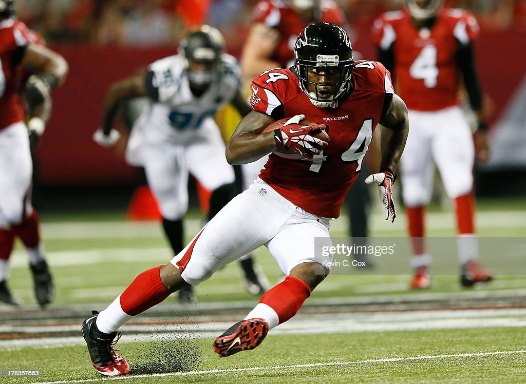 Jason Snelling of the Atlanta Falcons slips as he rushes a reception upfield against the Jacksonville Jaguars at Georgia Dome on August 29 2013 in...