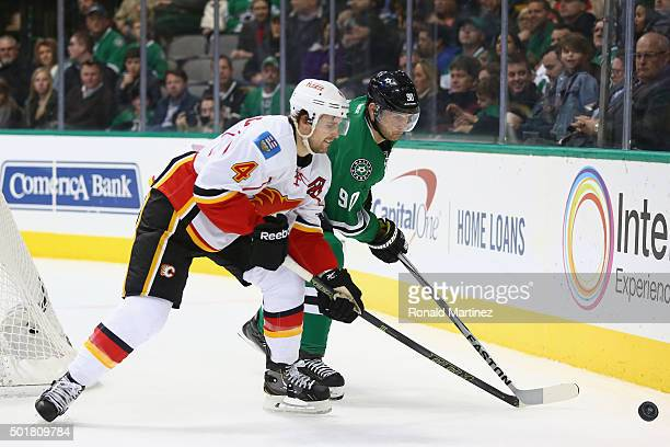 Jason Spezza of the Dallas Stars skates the puck against Kris Russell of the Calgary Flames in the first period at American Airlines Center on...