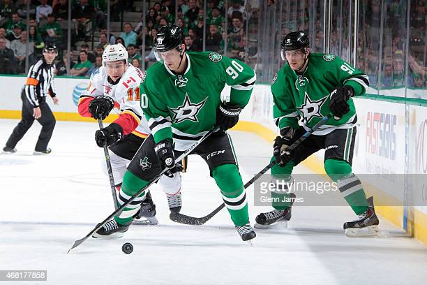 Jason Spezza of the Dallas Stars tries to keep the puck away against Mikael Backlund of the Calgary Flames at the American Airlines Center on March...