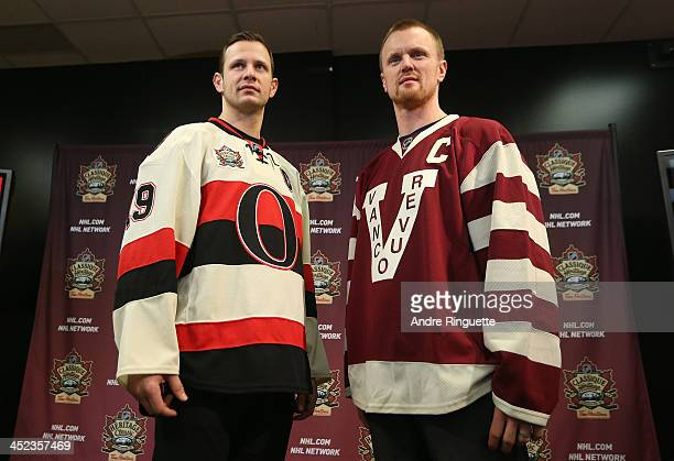 Jason Spezza of the Ottawa Senators and Henrik Sedin the Vancouver Canucks pose with NHL Heritage Classic jerseys during an official announcement at...