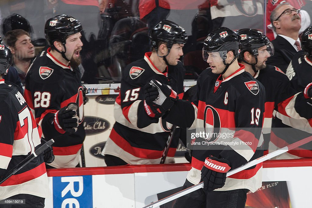 Jason Spezza of the Ottawa Senators celebrates his first period powerplay goal with team mates Matt Kassian and Zack Smith during an NHL game against...