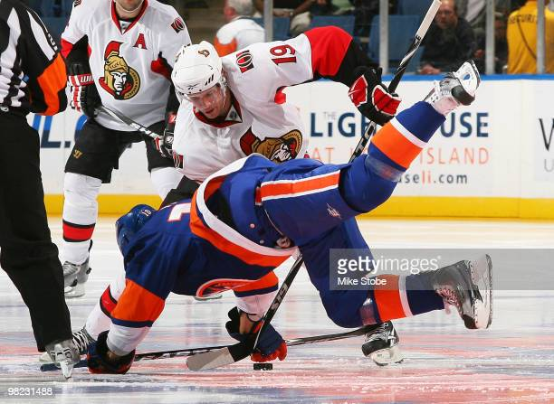 Jason Spezza of the Ottawa Senators goes for the puck as Richard Park of the New York Islanders falls to the ice on April 3 2010 at Nassau Coliseum...