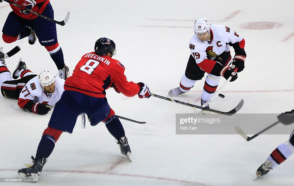 <a gi-track='captionPersonalityLinkClicked' href=/galleries/search?phrase=Jason+Spezza&family=editorial&specificpeople=202023 ng-click='$event.stopPropagation()'>Jason Spezza</a> #19 of the Ottawa Senators pass the puck in front of Alex Ovechkin #8 of the Washington Capitals during the third period at Verizon Center on November 27, 2013 in Washington, DC.