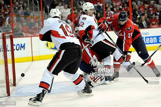 Jason Spezza of the Ottawa Senators scores a goal in the first period as Mike Fisher is pushed into Jose Theodore by Shaone Morrisonn of the...