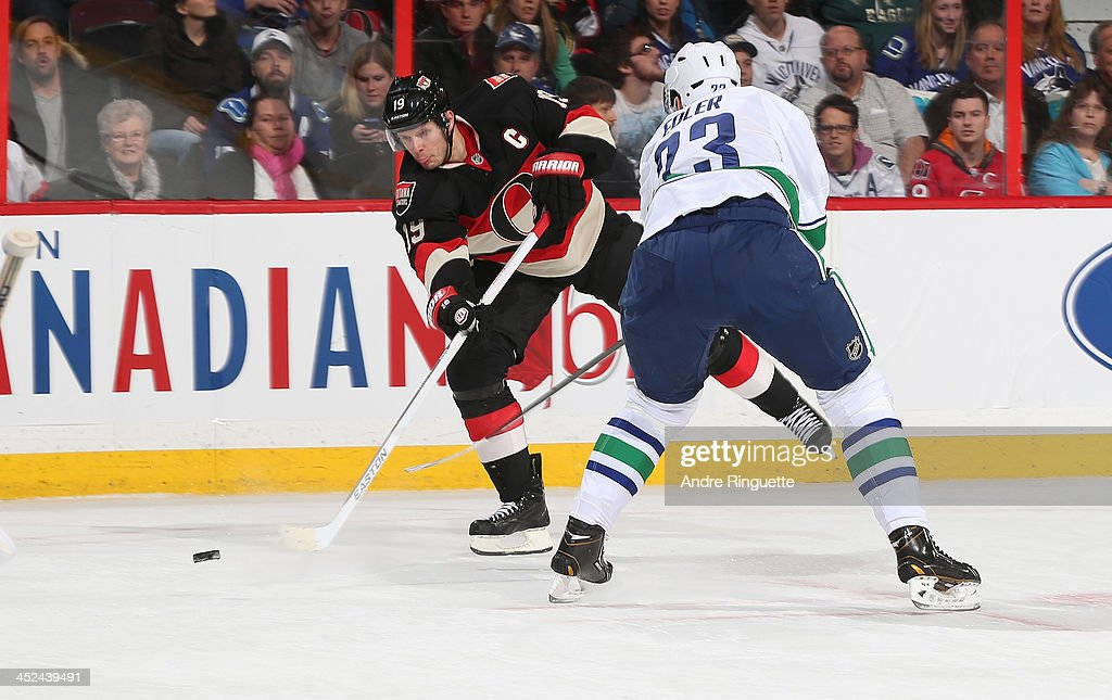 <a gi-track='captionPersonalityLinkClicked' href=/galleries/search?phrase=Jason+Spezza&family=editorial&specificpeople=202023 ng-click='$event.stopPropagation()'>Jason Spezza</a> #19 of the Ottawa Senators shoots the puck against <a gi-track='captionPersonalityLinkClicked' href=/galleries/search?phrase=Alexander+Edler&family=editorial&specificpeople=882987 ng-click='$event.stopPropagation()'>Alexander Edler</a> #23 of the Vancouver Canucks at Canadian Tire Centre on November 28, 2013 in Ottawa, Ontario, Canada.