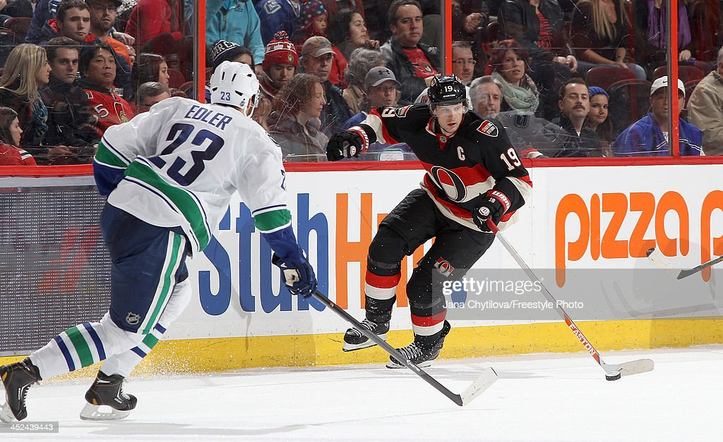 <a gi-track='captionPersonalityLinkClicked' href=/galleries/search?phrase=Jason+Spezza&family=editorial&specificpeople=202023 ng-click='$event.stopPropagation()'>Jason Spezza</a> #19 of the Ottawa Senators skates with the puck against <a gi-track='captionPersonalityLinkClicked' href=/galleries/search?phrase=Alexander+Edler&family=editorial&specificpeople=882987 ng-click='$event.stopPropagation()'>Alexander Edler</a> #23 of the Vancouver Canucks during an NHL game at Canadian Tire Centre on November 28, 2013 in Ottawa, Ontario, Canada.