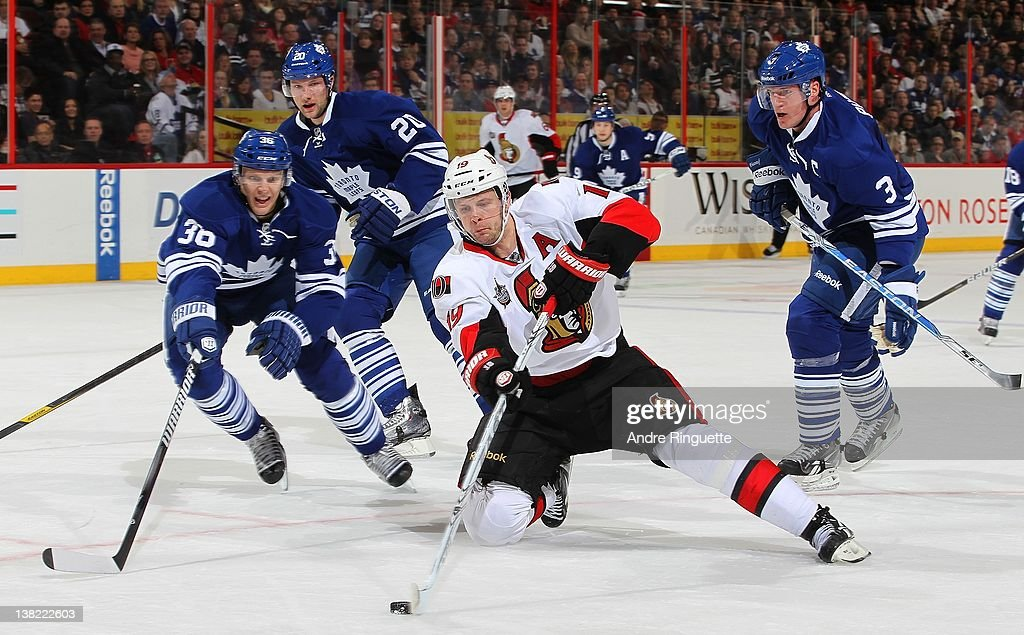 Jason Spezza of the Ottawa Senators takes a backhand shot from his knees against Carl Gunnarsson David Steckel and Dion Phaneuf of the Toronto Maple...