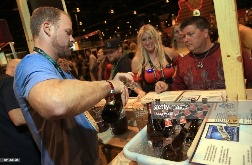 Jason Stillman of Blue Moon Brewing Company in Denver pours beers for Shawna Silber and Michael Bernard at the 32nd annual Great American Beer Festival at the Colorado Convention Center on October 10, 2013 in Denver, Colorado. The GABF runs October 10-12 and 49,000 attendees will be offered 3100 beers from 624 breweries.