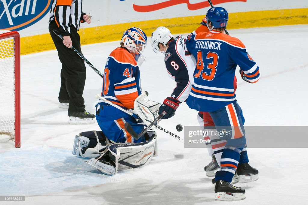 Jason Strudwick #43 and Devan Dubnyk #40 of the Edmonton Oilers defend against Scottie Upshall #8 of the Columbus Blue Jackets at Rexall Place on March 3, 2011 in Edmonton, Alberta, Canada.