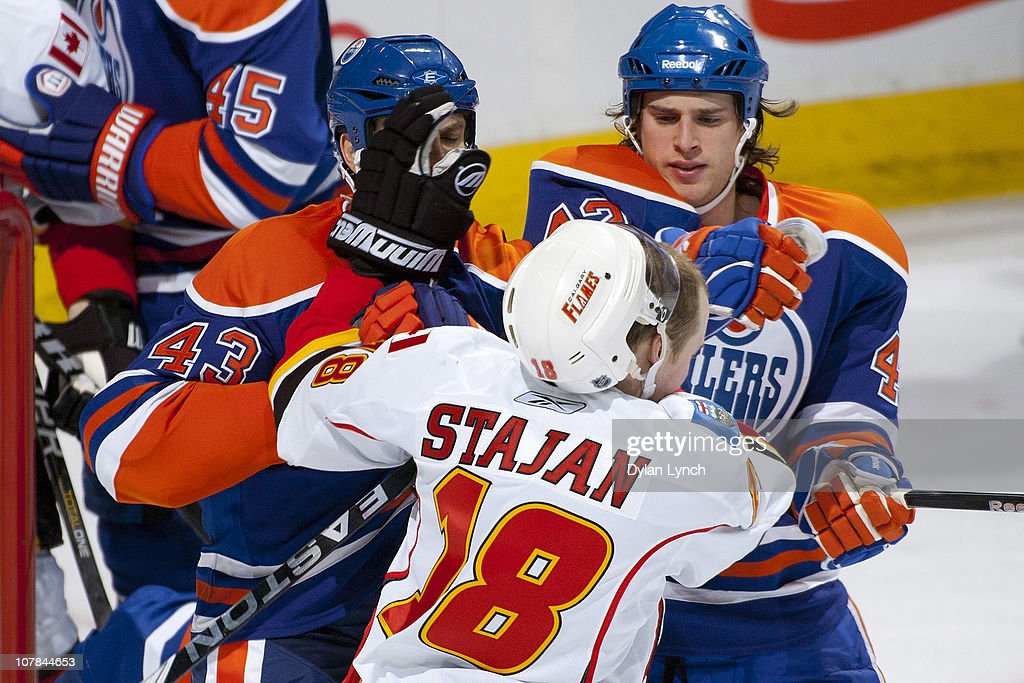 Jason Strudwick #43 and Ryan O'Marra #42 of the Edmonton Oilers jostle in a scrum with Matt Stajan #18 of the Calgary Flames at Rexall Place on January 1, 2011 in Edmonton, Alberta, Canada.
