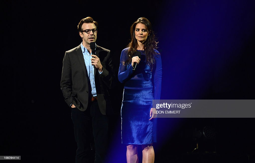 Jason Sudeikis (L) and Katie Holmes (R) speak on stage during '12-12-12 ~ The Concert For Sandy Relief' December 12, 2012 at Madison Square Garden in New York.