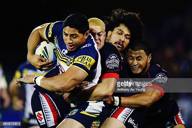 Jason Taumalolo of the Cowboys charges on against Tuimoala Lolohea Sione Lousi and Dominique Peyroux of the Warriors during the round 24 NRL match...