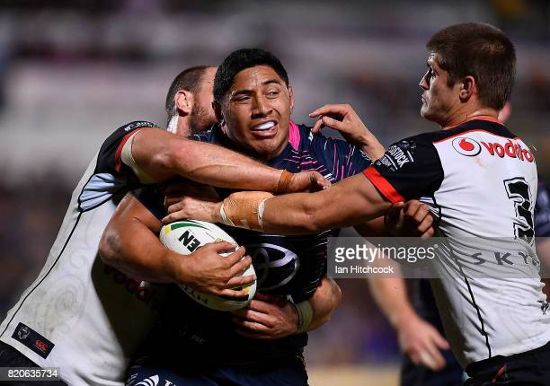 Jason Taumalolo of the Cowboys is tackled by Blake Ayshford and Simon Mannering of the Warriors during the round 20 NRL match between the North...