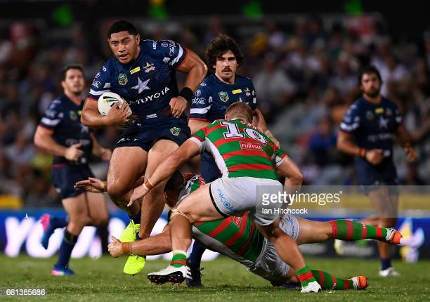 Jason Taumalolo of the Cowboys is tackled by Jason Clark and Tom Burgess of the Rabbitohs during the round five NRL match between the North...