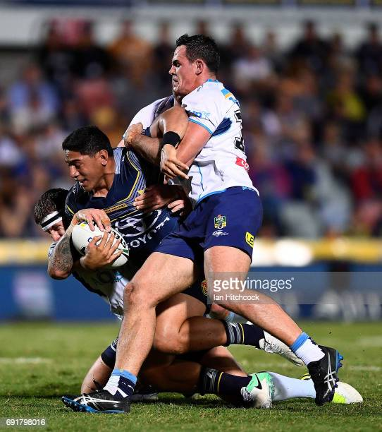 Jason Taumalolo of the Cowboys is tackled by Morgan Boyle and Jarrod Wallace of the Titans during the round 13 NRL match between the North Queensland...