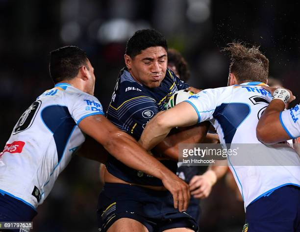Jason Taumalolo of the Cowboys is tackled by Ryan James and Max King of the Titans during the round 13 NRL match between the North Queensland Cowboys...