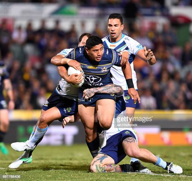Jason Taumalolo of the Cowboys is wrapped by the Titans defence during the round 13 NRL match between the North Queensland Cowboys and the Gold Coast...
