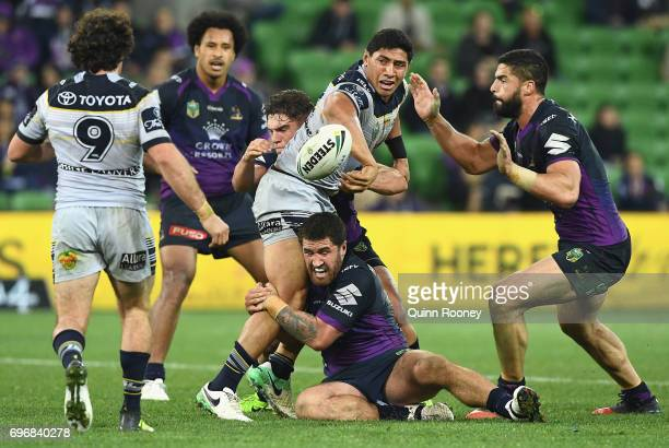 Jason Taumalolo of the Cowboys passes the ball whilst being tackled during the round 15 NRL match between the Melbourne Storm and the North...