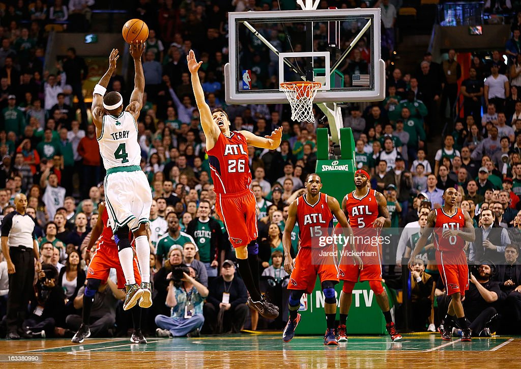 Jason Terry #4 of the Boston Celtics makes a three-point shot in the final minute of overtime in front of Kyle Korver #26 of the Atlanta Hawks during the game on March 8, 2013 at TD Garden in Boston, Massachusetts.