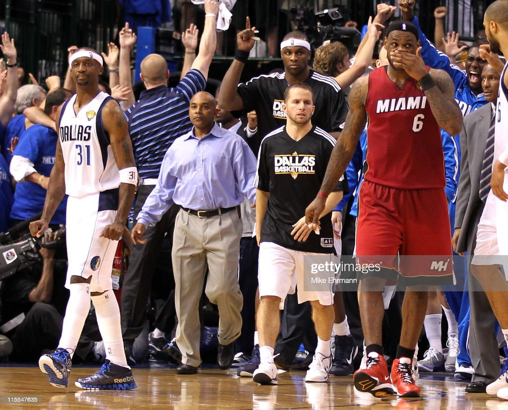 Jason Terry #31 of the Dallas Mavericks and his teammates react to their 86-83 win as LeBron James #6 of the Miami Heat walks off the court in Game Four of the 2011 NBA Finals at American Airlines Center on June 7, 2011 in Dallas, Texas.