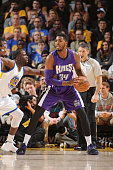Jason Thompson of the Sacramento Kings looks to pass against Draymond Green of the Golden State Warriors on December 22 2014 at Oracle Arena in...