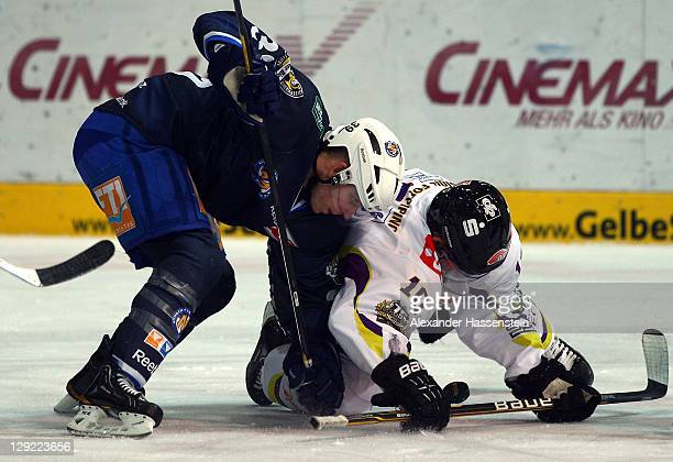 Jason Ulmer of Muenchen vies for the puck with Andreas Driendl of Krefeld during the DEL match between EHC Muenchen and Krefeld Pinguine at Olympia...