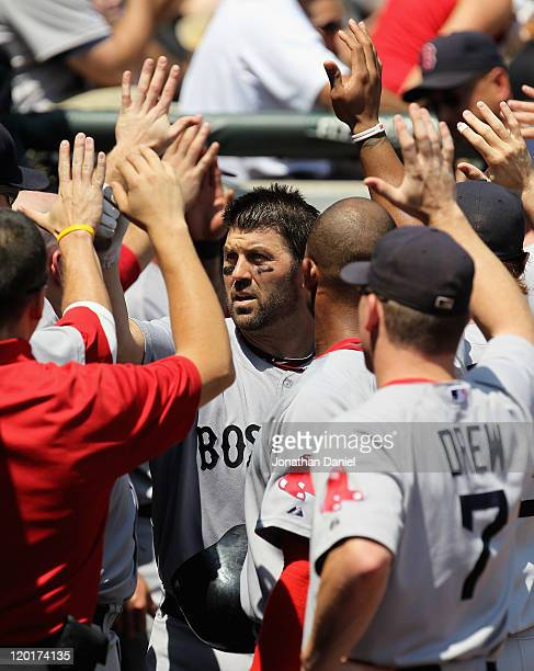 Jason Varitek of the Boston Red Sox is greeted by teammates in the dugout after hitting a tworun home run in the 2nd inning against the Chicago White...