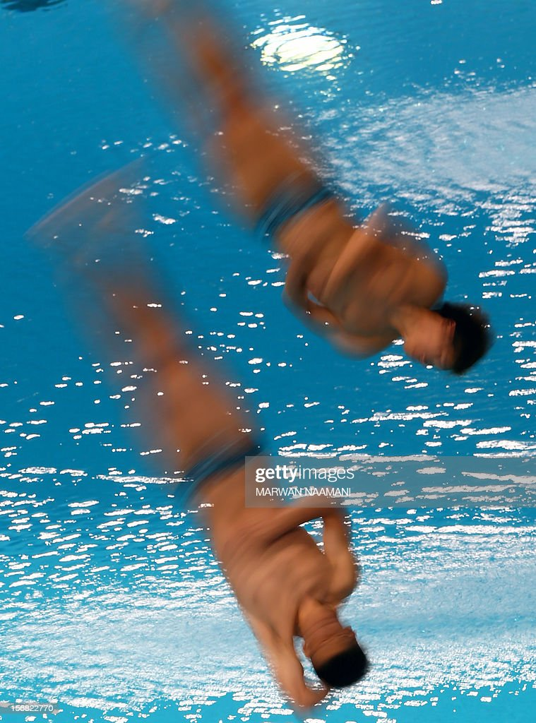 Jason Wai Ching Poon and Ho Wing Chow of Hong Kong perform in the men's synchronised 3m springboard diving comptition at the 9th Asian Swimming Championships in Dubai, on November 22, 2012. Hong Kong won the bronze meda in the event. AFP PHOTO/MARWAN NAAMANI