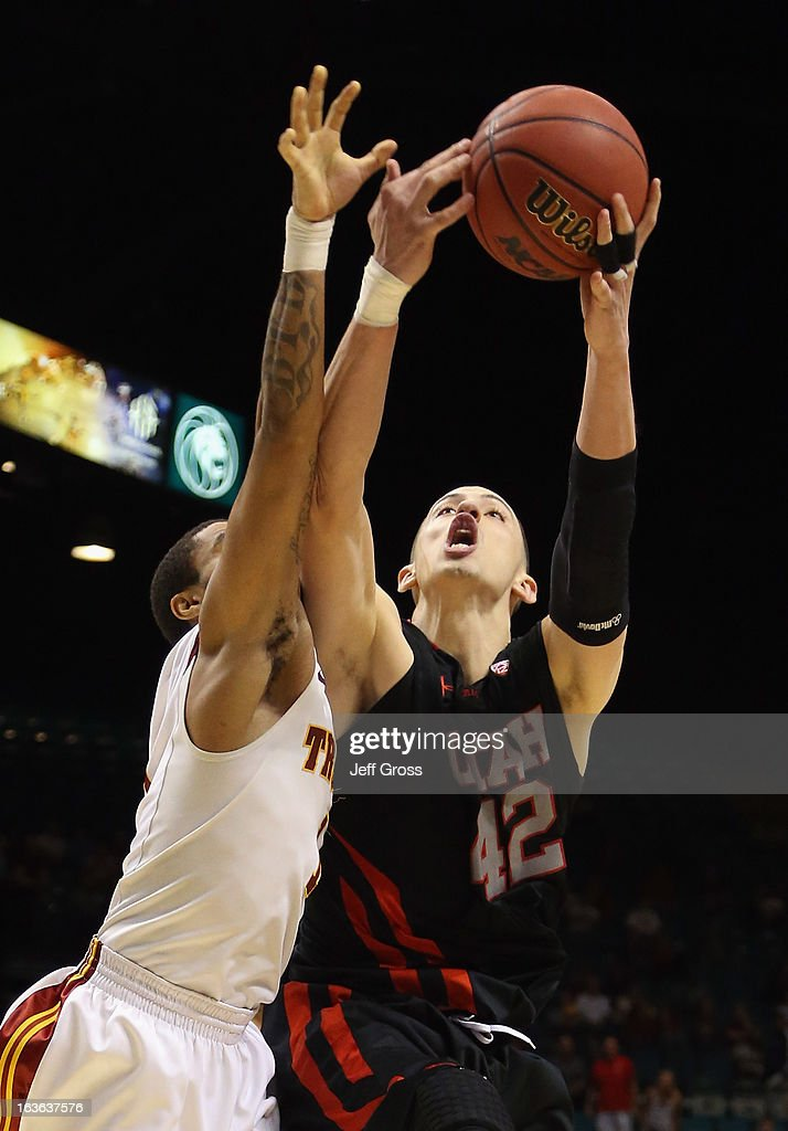 Jason Washburn #42 of the Utah Utes pulls a rebound away from Jio Fontan #1 of the USC Trojans in the second half during the first round of the Pac 12 Tournament at the MGM Grand Garden Arena on March 13, 2013 in Las Vegas, Nevada. Utah defeated USC