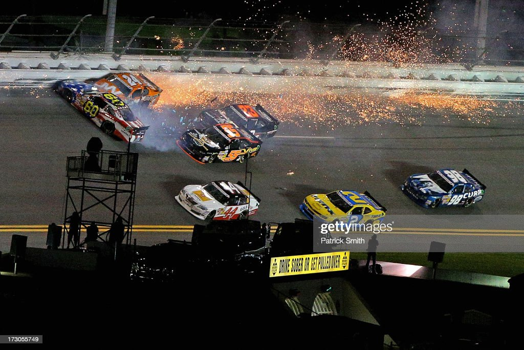 Jason White, driver of the #24 JW Demolition Toyota, and Travis Pastrana, driver of the #60 Roush Fenway Racing / RaceTrac Ford, are involved in an incident during the NASCAR Nationwide Series Subway Firecracker 250 at Daytona International Speedway on July 5, 2013 in Daytona Beach, Florida.