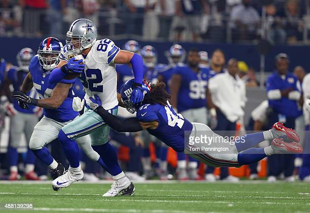 Jason Witten of the Dallas Cowboys carries the ball against Jasper Brinkley of the New York Giants and Uani' Unga of the New York Giants in the...