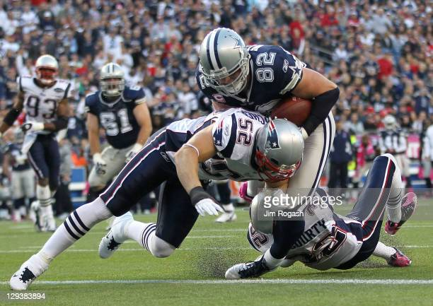Jason Witten of the Dallas Cowboys scores a touchdown against the defense of Dane Fletcher and Devin McCourty of the New England Patriots in the...