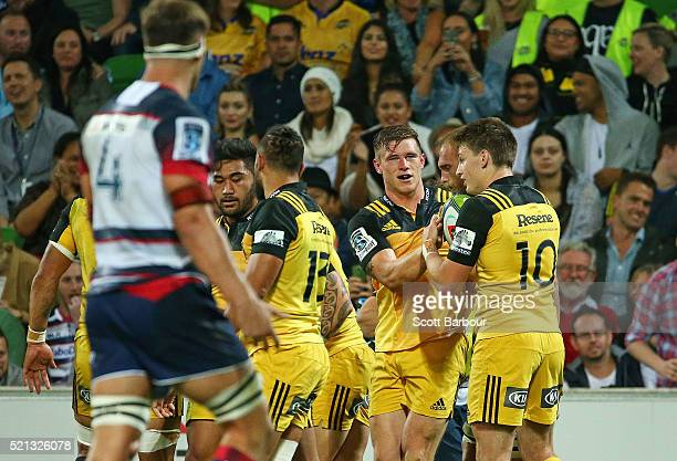 Jason Woodward of the Hurricanes is congratulated his teammates after scoring a try during the round eight Super Rugby match between the Rebels and...