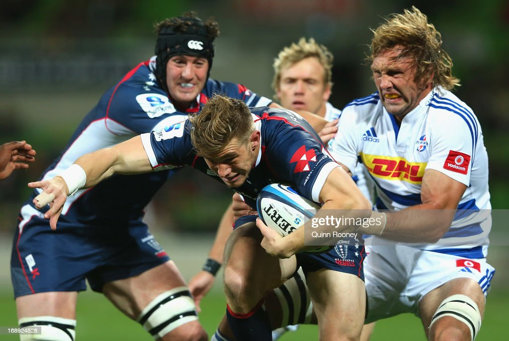 Jason Woodward of the Rebels is tackled by Andries Bekker of the Stormers during the round 14 Super Rugby match between the Rebels and the Stormers...