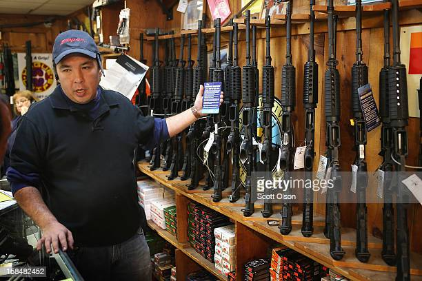 Jason Zielinski shows a customer a selection of AR15 style rifles being offered for sale at Freddie Bear Sports sporting goods store on December 17...