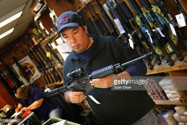 Jason Zielinski shows a customer an AR15 style rifle at Freddie Bear Sports sporting goods store on December 17 2012 in Tinley Park Illinois...