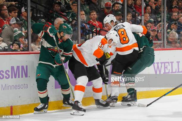Jason Zucker and Eric Staal of the Minnesota Wild battle for the puck with Jori Lehtera and Robert Hagg of the Philadelphia Flyers during the game at...