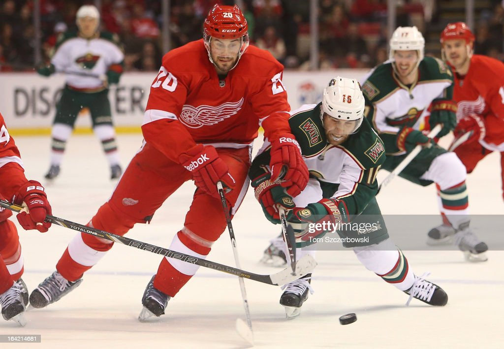 Jason Zucker #16 of the Minnesota Wild and Drew Miller #20 of the Detroit Red Wings chase the puck in NHL action at Joe Louis Arena on March 20, 2013 in Detroit, Michigan.