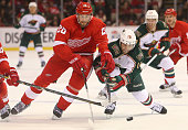 Jason Zucker of the Minnesota Wild and Drew Miller of the Detroit Red Wings chase the puck in NHL action at Joe Louis Arena on March 20 2013 in...